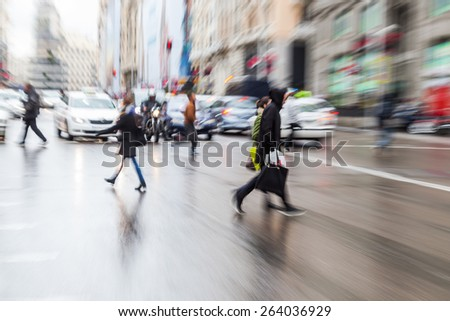 picture with camera made zoom effect of people crossing a rainy street