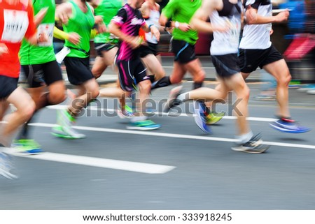 picture with creative motion blur effect made by camera of running people at a city marathon - stock photo