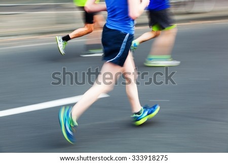 picture with creative motion blur effect made by camera of running people at a city marathon