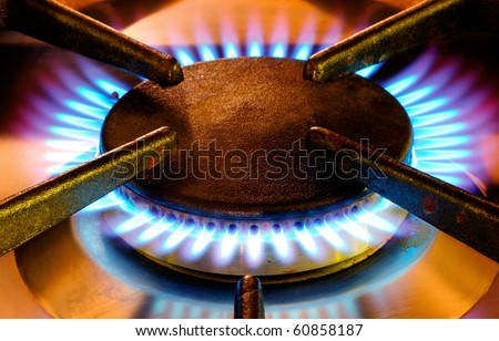 Picture with warm colors of an old gas cooker hob in full operation - stock photo
