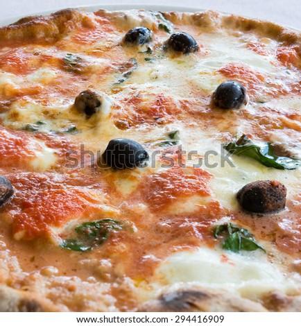 Pictured wheat pizza with olives tomato basil and mozzarella Neapolitan (bufala) - stock photo