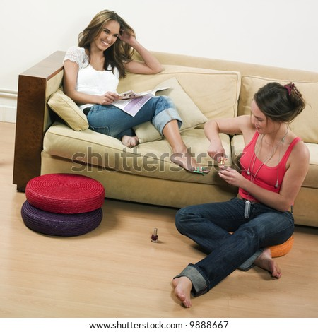 pictures in a living room of two young girls sitting on a couch - stock photo