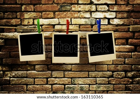 pictures on a rope with clothespins, with clipping path for images, in front of a brick wall - stock photo