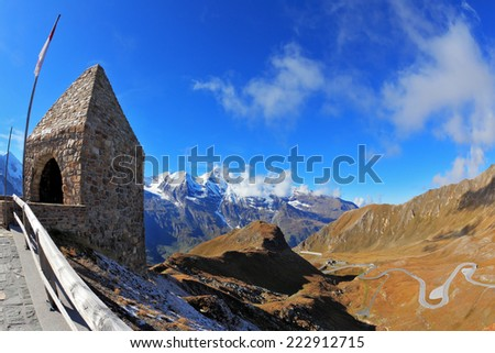 Picturesque alpine road Grossgloknershtrasse. Bright sunny day. Steep slopes are marked with red flags. Photo taken by lens Fisheye - stock photo