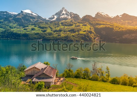 Picturesque alpine scenery warmed up by sunlight -  Lovely vacation destination in the Swiss Alps, around the Walensee lake. A spring scenery with mountains, lake, meadows and warm sun. - stock photo