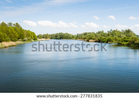 Picturesque and soothing view of a wide creek in a large nature reserve on a sunny day in the spring season. - stock photo