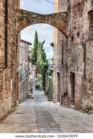 picturesque antique narrow alley with arch in Todi, Umbria, Italy - stock photo