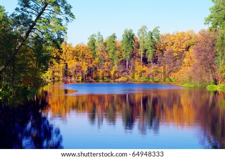 Picturesque autumn landscape of river and boat