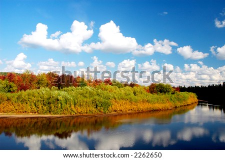 Picturesque autumn landscape - river and bright trees. blue sky with clouds. - stock photo