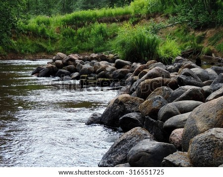 Picturesque beautiful view of a dynamic watercourse of river after a small stone threshold. Karelia, Russia.