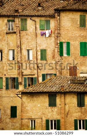 Picturesque building facades in  Siena Italy, with windows, shutters and tile roofs.