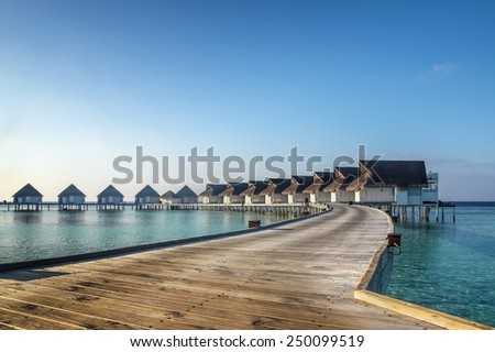 Picturesque bungalows on stilts near the shore of a tropical island, Maldives - stock photo