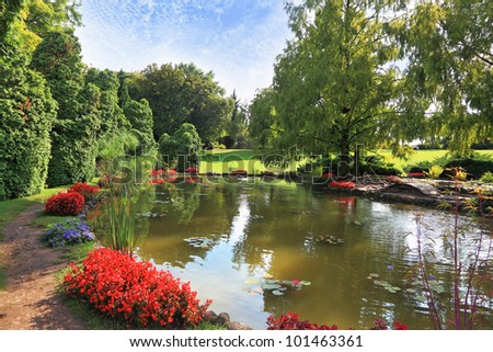 Picturesque bushes with red flowers at a silent pond. Charming park Sigurta in northern Italy.