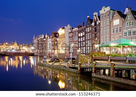Picturesque city of Amsterdam in Holland, Netherlands at night with historic Dutch style row houses by the canal. - stock photo