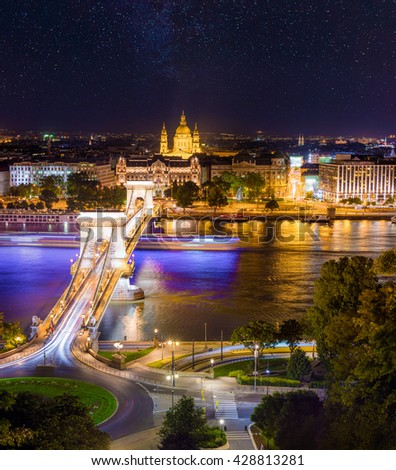 Picturesque cityscape of centered Saint Stephen's Basilica (St Istvan's church) and Chain Bridge on the Danube river. Starry night in Budapest, Hungary, Europe. Artistic style post processed photo.
