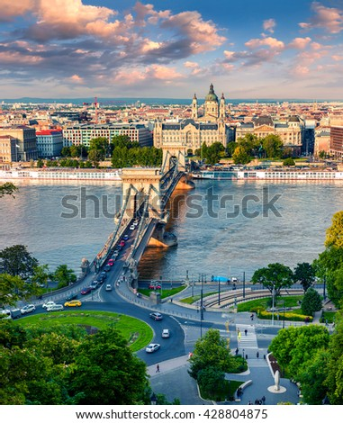 Picturesque cityscape of Saint Stephen's Basilica church (St Istvan's church) and Chain Bridge on the Danube river. Colorful sunset in Budapest, Hungary, Europe. Artistic style post processed photo. - stock photo