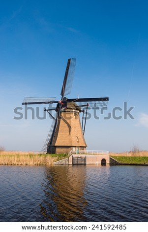 Picturesque Dutch windmill next to a canal on a sunny day in springtime. - stock photo