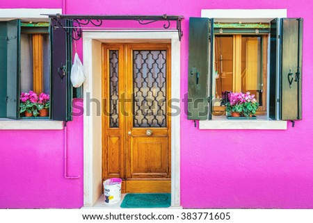 Picturesque entrance door,windows with green shutters and paint basket on pink wall of houses on the famous island Burano, Venice, Italy - stock photo