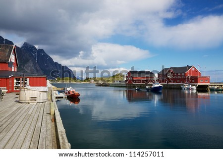 Picturesque fishing port in town of Henningsvaer on Lofoten islands in Norway with typical red wooden buildings and small fishing boats - stock photo