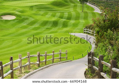 Picturesque green golf field with a wooden fence - stock photo
