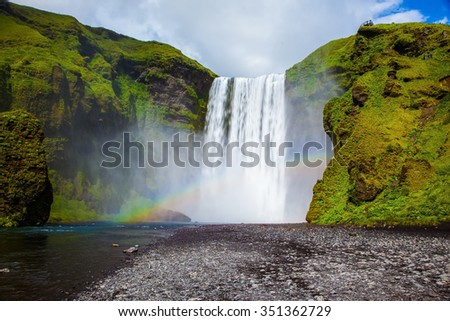 Picturesque huge rainbow appears in the water mist. The most popular waterfall in Iceland - Skogafoss. Water rushes down with a crash, forming a cloud of mist - stock photo
