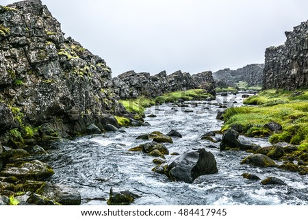 Picturesque icelandic river with moss rocks and grey sky in summer