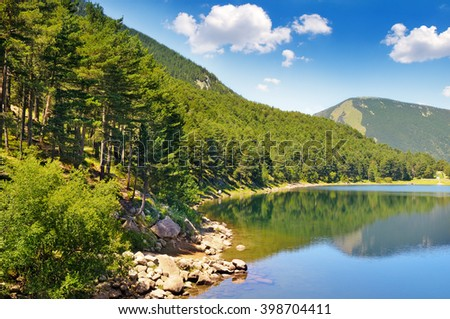picturesque lake, mountains and blue sky - stock photo
