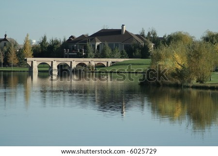 picturesque lake with autumn colors, aquaduct, reflection and luxury home - stock photo