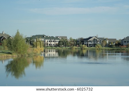 picturesque lake with luxury homes - stock photo