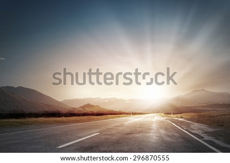 Picturesque landscape scene and sunrise above road - stock photo