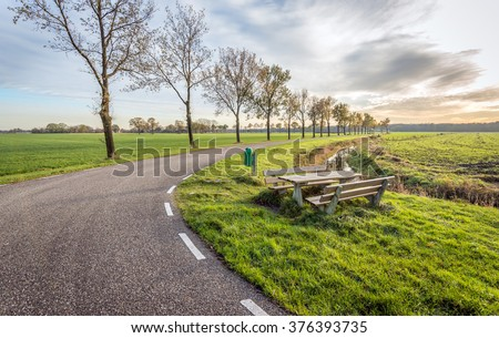 Picturesque landscape with an asphalt road through a rural area with a row of bare trees. In the side of the road is a wooden picnic table and bench. It's autumn now. - stock photo
