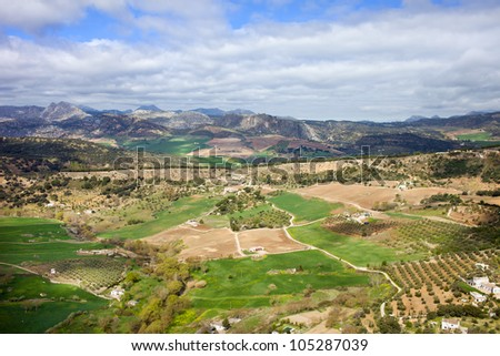 Picturesque landscape with cultivated fields and green meadows of hilly Andalusia countryside in southern Spain. - stock photo