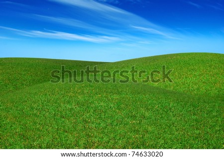 Picturesque landscape with green field and blue sky - stock photo