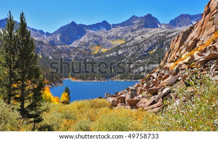 Picturesque mountain lake and fur-trees on its coast