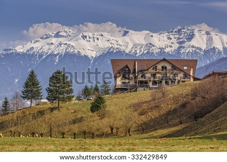 Picturesque mountain landscape with modern chalet and snowy Bucegi mountains in spring, Romania. Scenic touristic vacation destinations. - stock photo