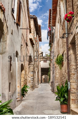 picturesque narrow alley with ancient arch, underpass, plants and flowers in Bevagna, Umbria, Italy - stock photo