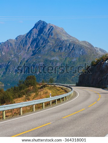 Picturesque Norway road landscape on high mountains, lake and fjord with blue sky in summer day, Norge.