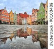 Picturesque old gothic houses reflecting in a puddle in a german city near Munich - stock photo