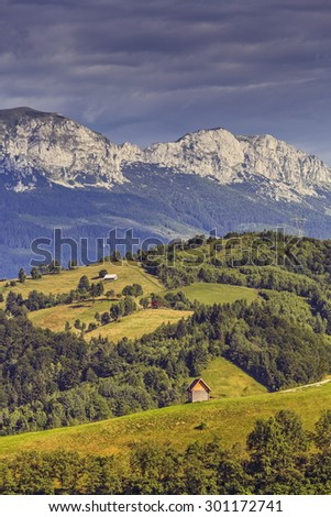 Picturesque rural scenery with remote traditional Romanian houses scattered uphill near Bucegi mountains in Moeciu village, Brasov county, Romania. Travel destinations. - stock photo