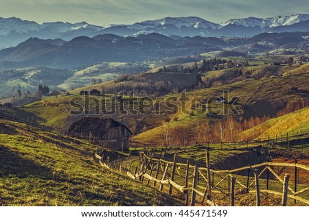 Picturesque spring rural scenery with traditional Romanian wooden house and country road uphill in Sirnea village, Brasov county, Romania. Travel destinations. - stock photo