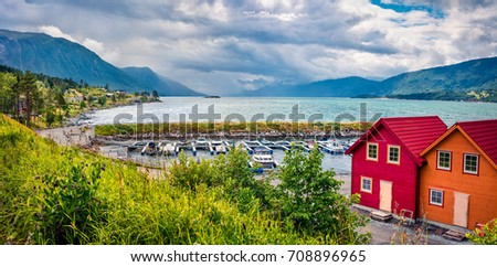 Picturesque summer view of typical Norwegian village on the shore of fjord. Traveling concept background.