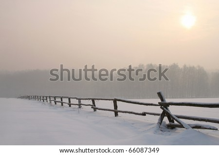 Picturesque sunrise over the field with idyllic fence in the foreground. - stock photo