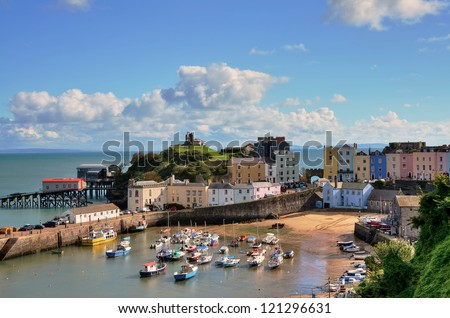 Picturesque view of boats in Tenby Harbour, with its clusters of colourful painted houses, and Castle Hill - stock photo