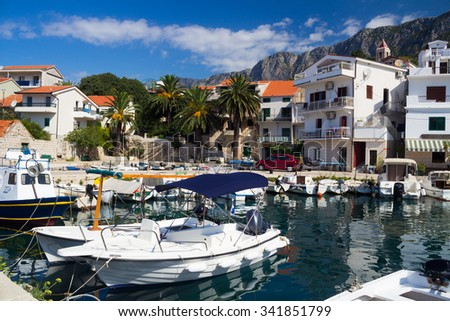 Picturesque view of harbor with a lot of boats, houses, palm trees and mountains in the background, Gradac, Croatia - stock photo