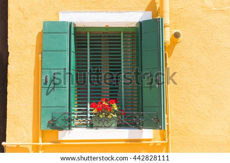 Picturesque window with shutters and flowers on yellow wall of houses on the famous Burano island. Venice, Italy, Europe - stock photo