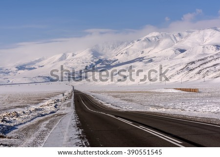 Picturesque winter view with asphalt road across the steppe, mountains covered with snow and trees on the background of blue sky and clouds - stock photo