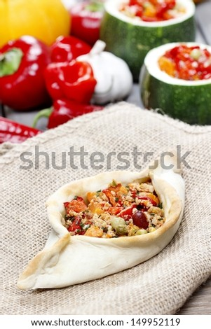 Pide, also known as Pita in some countries, is a dish similar to pizza, typically served as a part of Turkish, Armenian and Middle-Eastern cuisines. - stock photo