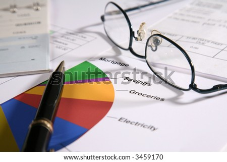 Pie chart with red, green, blue, yellow, orange, eye glasses and checkbook and bills - stock photo