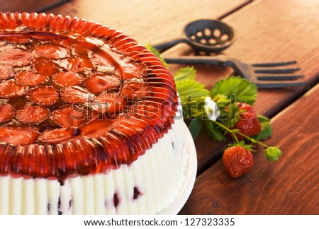 Pie the decorated jelly from a strawberry on a wooden table - stock photo
