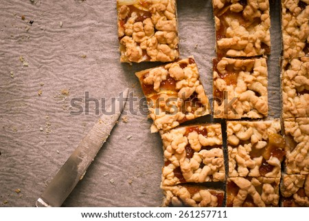Pie with apples and apricot jam cut into pieces on a baking. Image tinting - stock photo